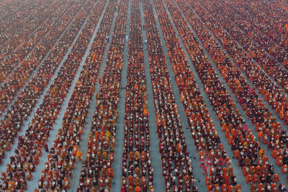 A handout photo taken on December 8, 2019 and released by Dhammakaya Fondation shows monks lining up for alms during the alms-giving ceremony to 30,000 monks organized by the region government of Mandalay affiliated with Dhammakaya Foundation at Chan