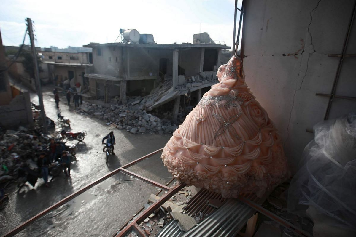 A wedding dress is seen in the destroyed window of a bridal shop in a damaged building in Balyun in Syria's northwestern Idlib province, on December 8, 2019, the day after a reported Russian airstrike on a market in the village. PHOTO: AFP