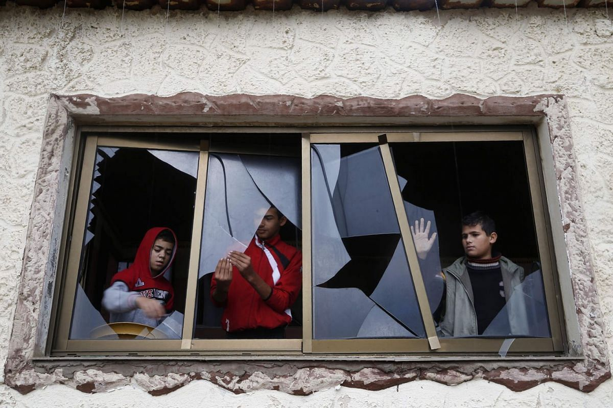 Palestinian boys pull shards of glass from a broken window at their home near the site of Israeli overnight attacks in Gaza City on December 8, 2019. PHOTO: AFP