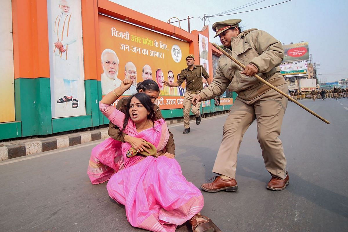 A Samajwadi Party activist (C in pink) is being held by police personnel as she protests against the Unnao rape case during a demonstration at Vishan Sabha, the seat of the legislature of Uttar Pradesh state, in Lucknow on December 7, 2019. PHOTO: AF