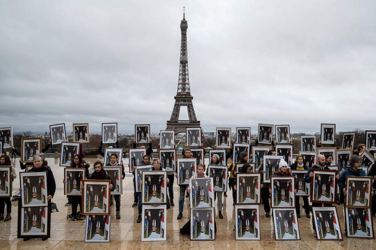 French climate activists of the Nonviolent Action COP21 (ANV-COP21) association hold upside down official portraits of French President Emmanuel Macron, after they were unhooked from town halls across the country, at the Trocadero esplanade in front