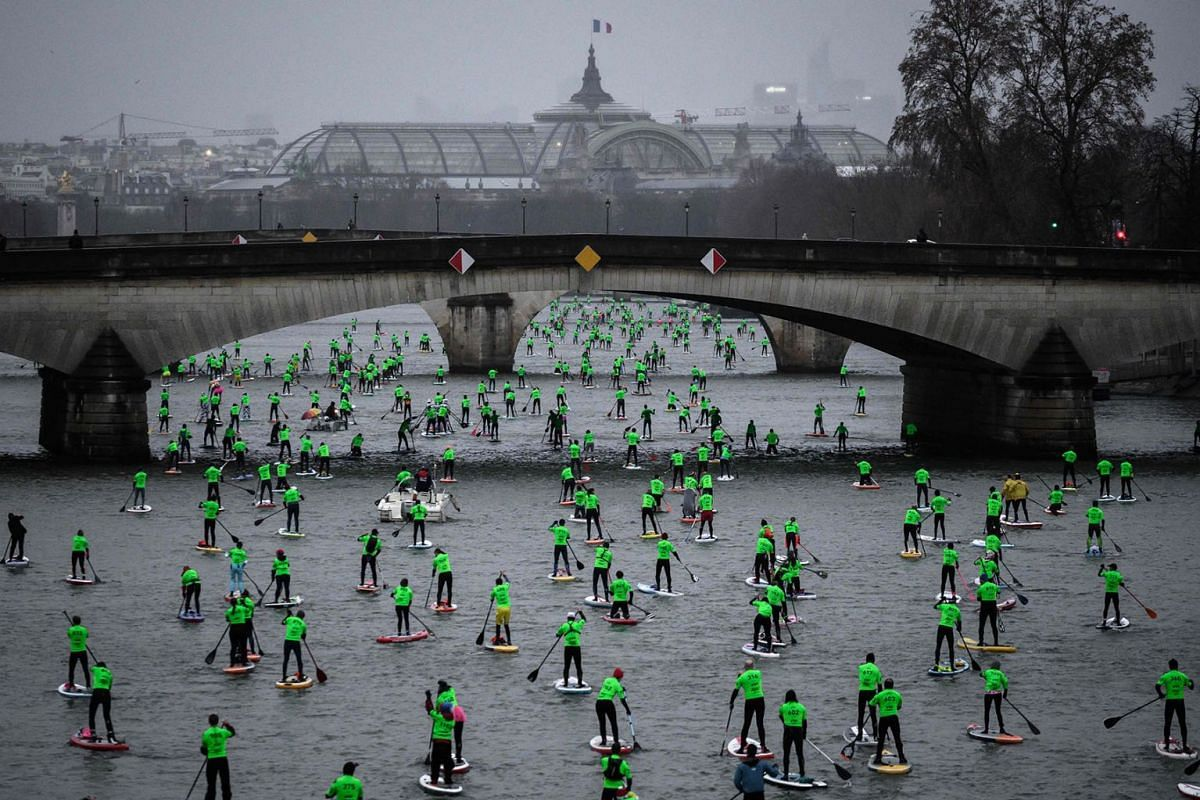 Competitors take part in the Nautic Paddle Race on the Seine river with The Grand Palais in the background in Paris on December 8, 2019. PHOTO: AFP