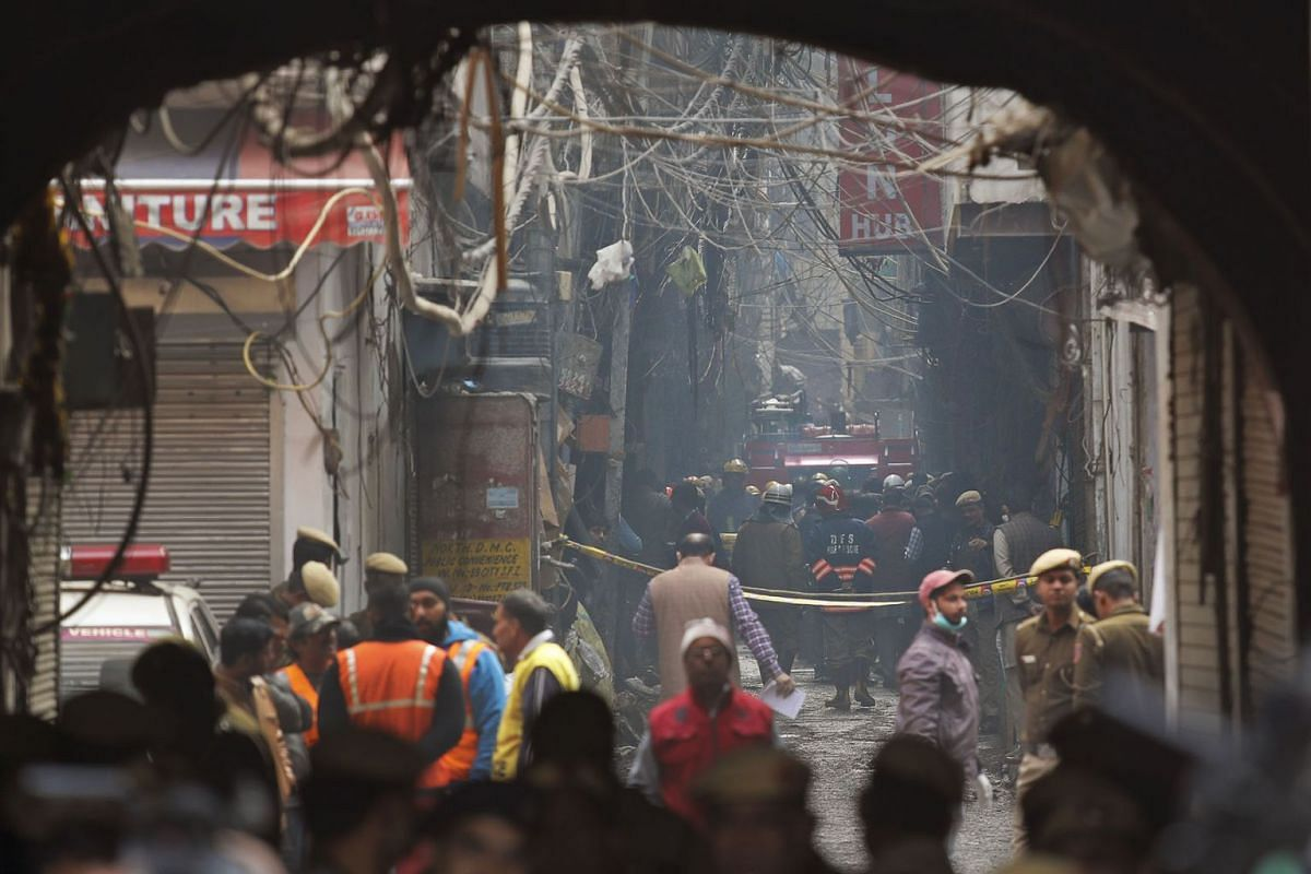 A fire engine stands by the site of a fire in an alleyway, tangled in electrical wire and too narrow for vehicles to access, in New Delhi, India, Sunday, Dec. 8, 2019. Dozens of people died on Sunday in a devastating fire at a building in a crowded g