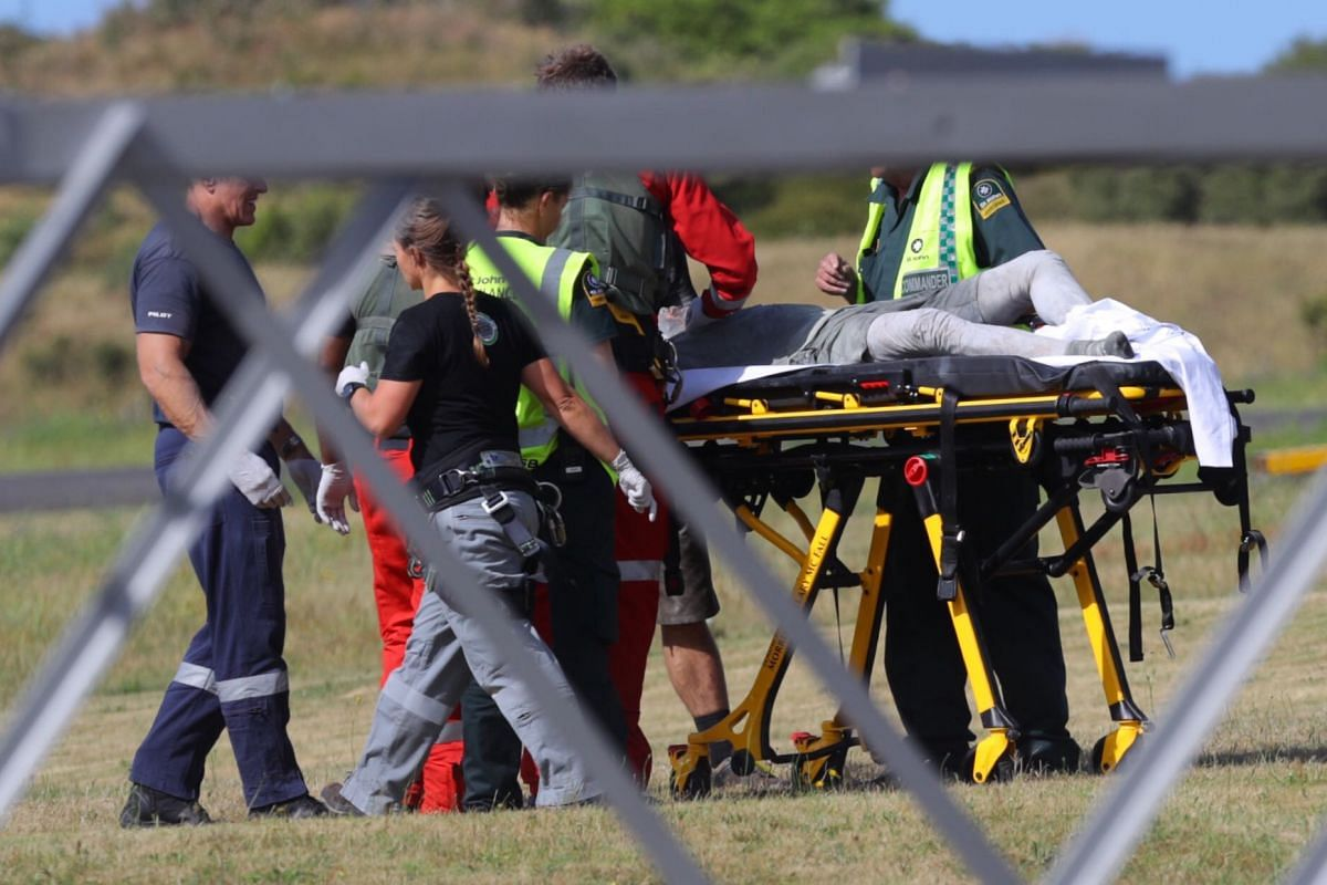 Emergency service personnel attend to an injured person arriving at the Whakatane Airfield after the volcanic eruption on White Island.