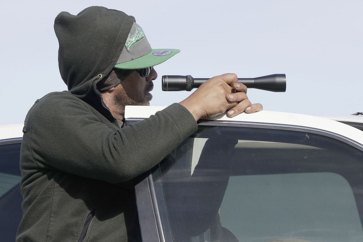 A man on the waterfront in Whakatane, New Zealand, using a scope to look at White Island on Dec 10, 2019.