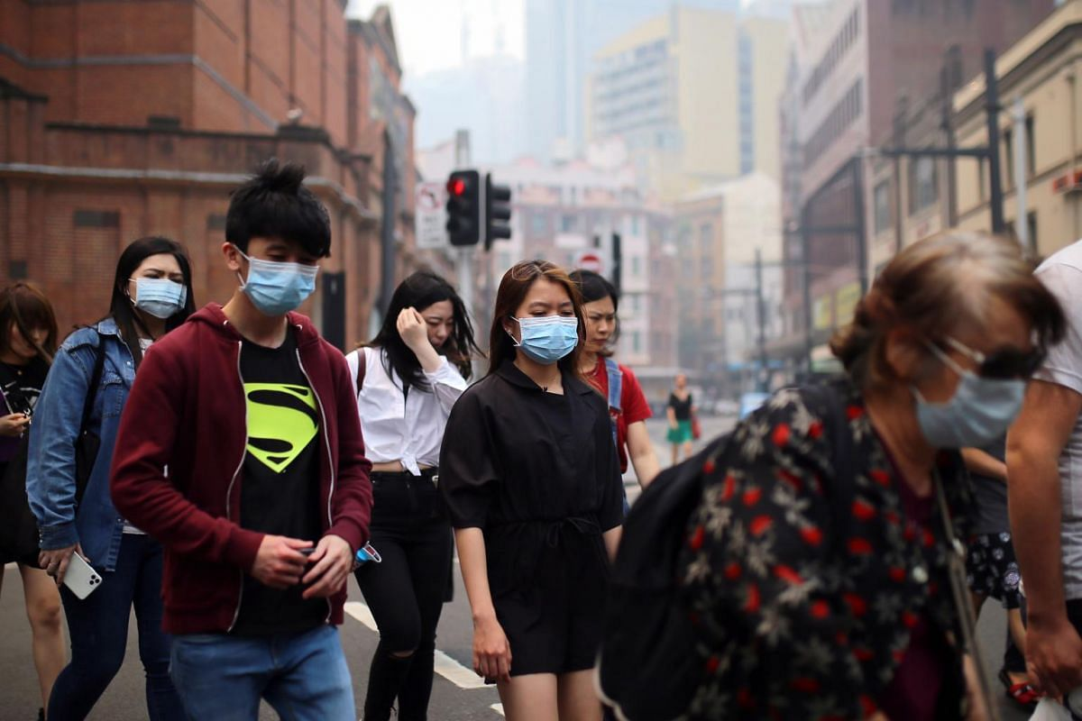 Pedestrians wear masks as smoke and haze from bushfires in New South Wales blankets the Central Business District in Sydney on Dec 10, 2019.