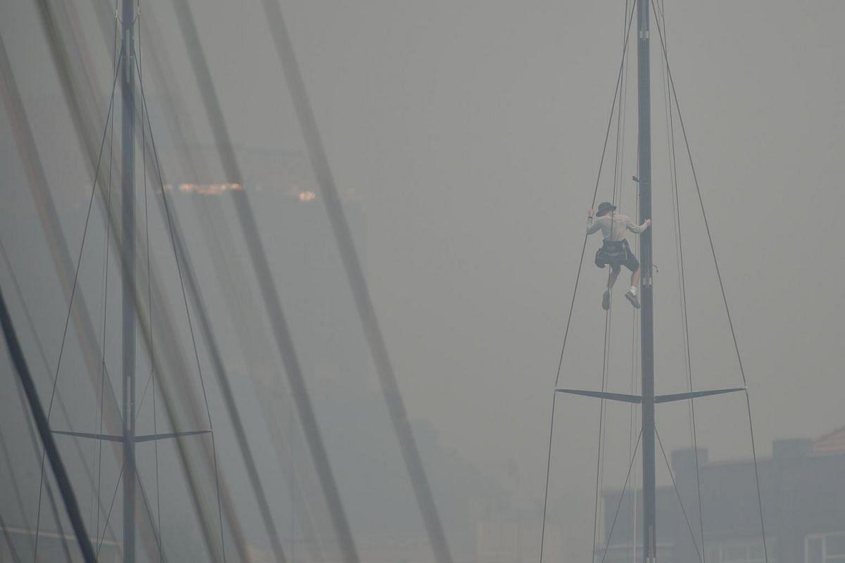 A sailor climbs the mast of a yacht at the Cruising Yacht Club of Australia in Sydney on Dec 10, 2019.
