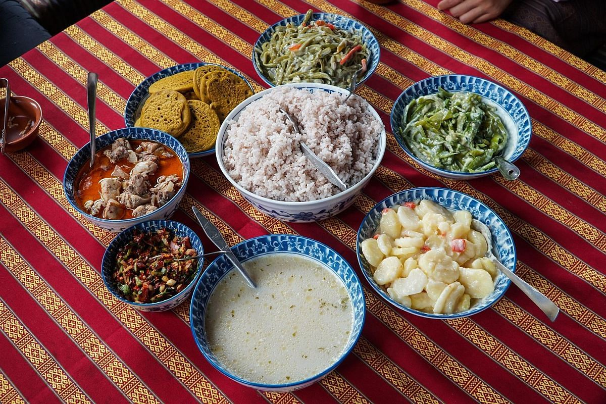 Meals often include an assortment of dishes cooked with chilli and cheese, accompanied by red rice.