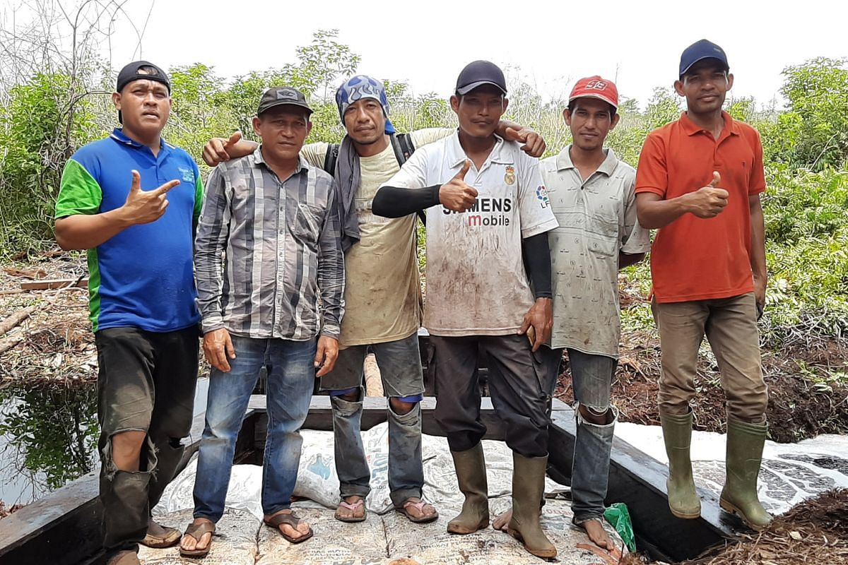 A firefighting team in Terkul village, Riau province. With the aid of Indonesia's Peatland Restoration Agency (BRG) - which was set up in 2016 to restore carbon-rich peatland damaged by fires - the villagers have built 11 dams on community land since