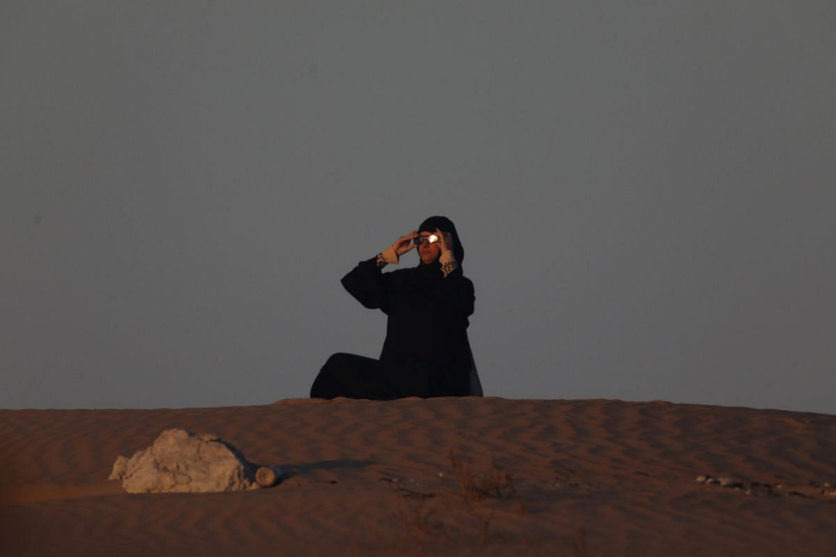 An Emirati woman views an annular solar eclipse in Abu Dhabi, United Arab Emirates, on Dec 26, 2019.