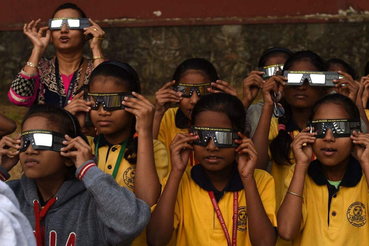 "Students use solar filter glasses to view a rare ""ring of fire"" solar eclipse at a school in Mumbai, India, on Dec 26, 2019."