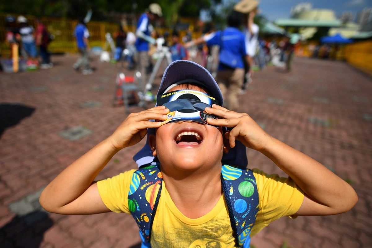 Six-year-old Gideon Chew watching the eclipse with his solar eclipse viewer at Science Centre Singapore on Dec 26, 2019.