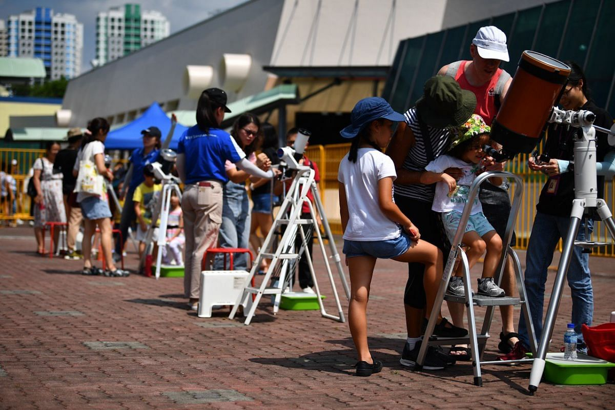 People viewing the solar eclipse through telescopes at Science Centre Singapore on Dec 26, 2019.