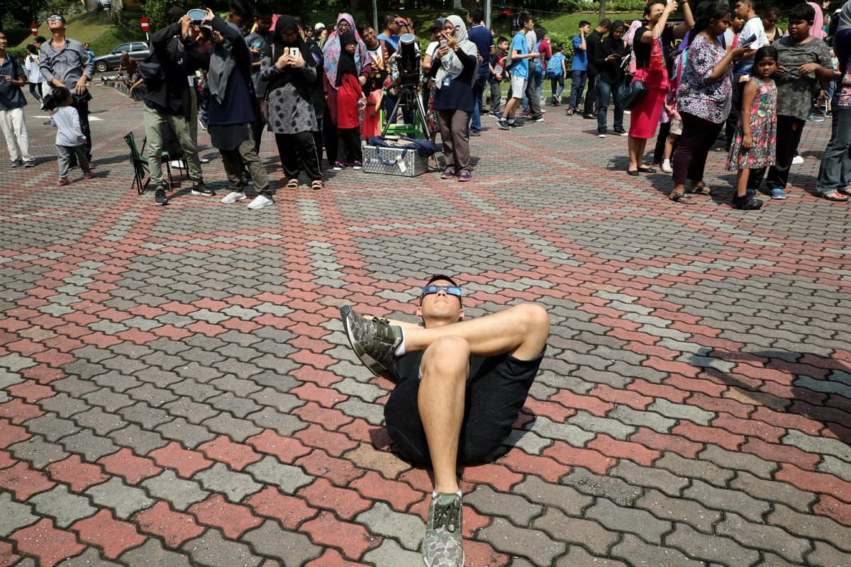 A visitor at the planetarium in Kuala Lumpur makes himself comfortable to view the partial solar eclipse on Dec 26, 2019.