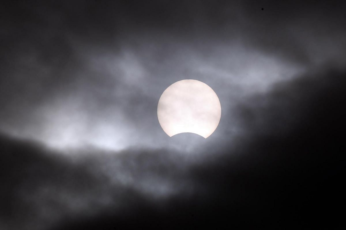 A partial solar eclipse is visible through clouds in Seoul, South Korea, on Dec 26, 2019.