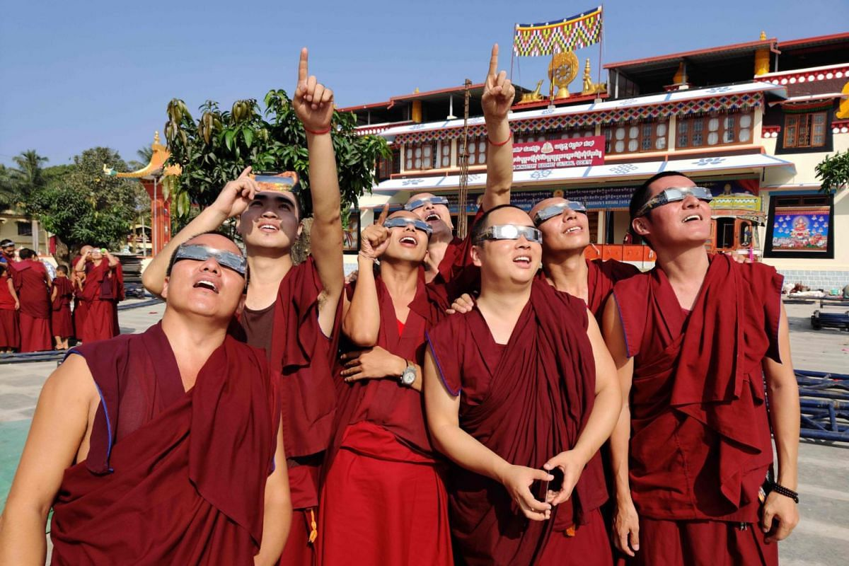 "Monks wearing solar filter glasses watch a ""ring of fire"" solar eclipse at the Gaden monastery in a Tibetan colony in Teginkoppa, on Dec 26, 2019."