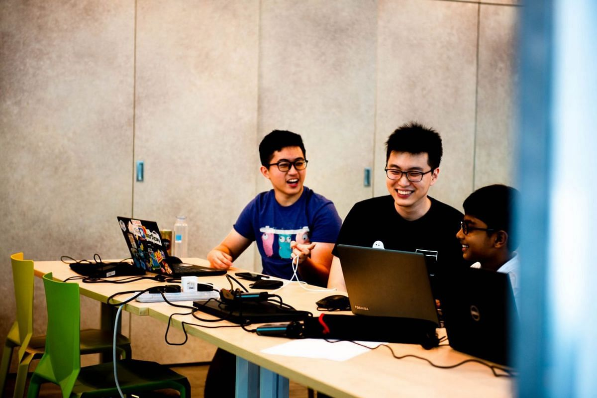 Volunteer instructors Andrew Wirawan Sutjipto (far left) and Teng Hao teaching the Python programming language during a Code in the Community class by Saturday Kids.