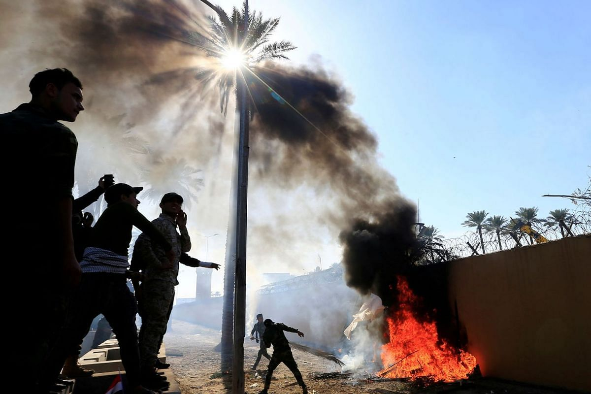 Hashd al-Shaabi (paramilitary forces) fighters set fire on the U.S. Embassy wall to condemn air strikes on their bases, in Baghdad, Iraq December 31, 2019. PHOTO: REUTERS