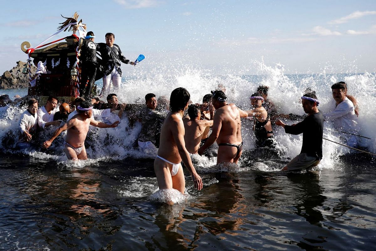 """Worshipers carry a """"mikoshi"""" or portable shrine in the sea during a festival to wish for calm waters in the ocean and good fortune in the new year in Oiso, Kanagawa prefecture, west of Tokyo, Japan, January 1, 2020. PHOTO: REUTERS"""