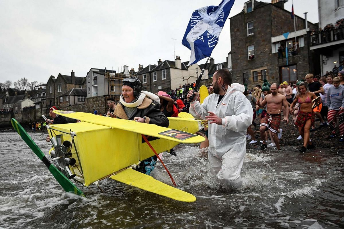 """Participants take part in the annual New Year's Day """"Loony Dook"""" swim, in the Firth of Forth, in South Queensferry, near Edinburgh, on January 1, 2020. PHOTO: AFP"""