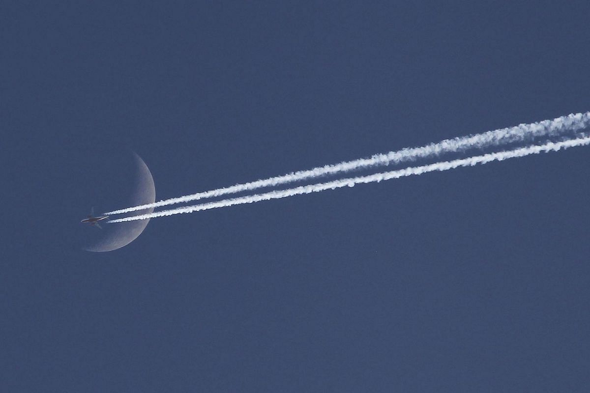An aircraft flies past the moon during the last day of 2019 on the outskirts of Chandigarh on December 31, 2019. PHOTO: AFP