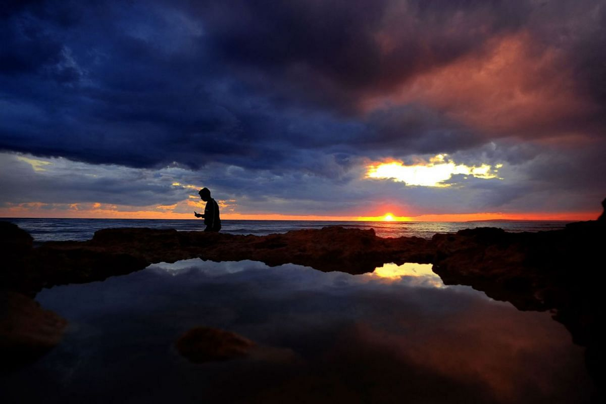 A boy takes pictures by the sea during sunset in the southeast resort of Ayia Napa in the eastern Mediterranean island of Cyprus, Wednesday, Jan. 1, 2020. PHOTO: AP