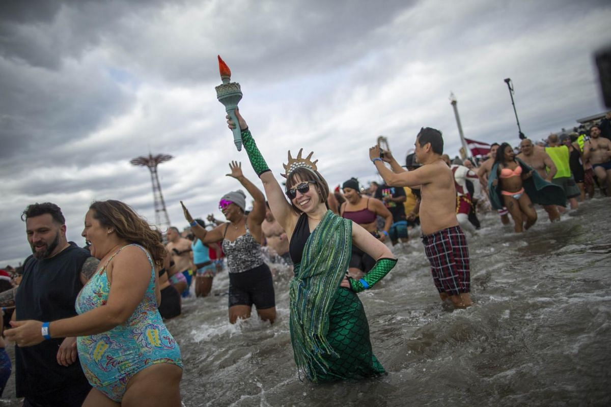 A woman dressed as Statue of Liberty joins participants as they run into the Atlantic ocean during the annual Polar Bear plunge on Coney Island.