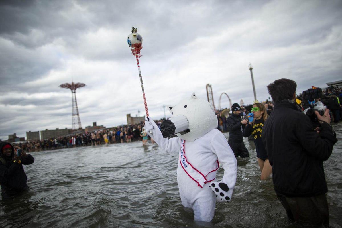 A man dressed as a polar bear joins participants as they run into the Atlantic ocean during the annual Polar Bear plunge on Coney Island.