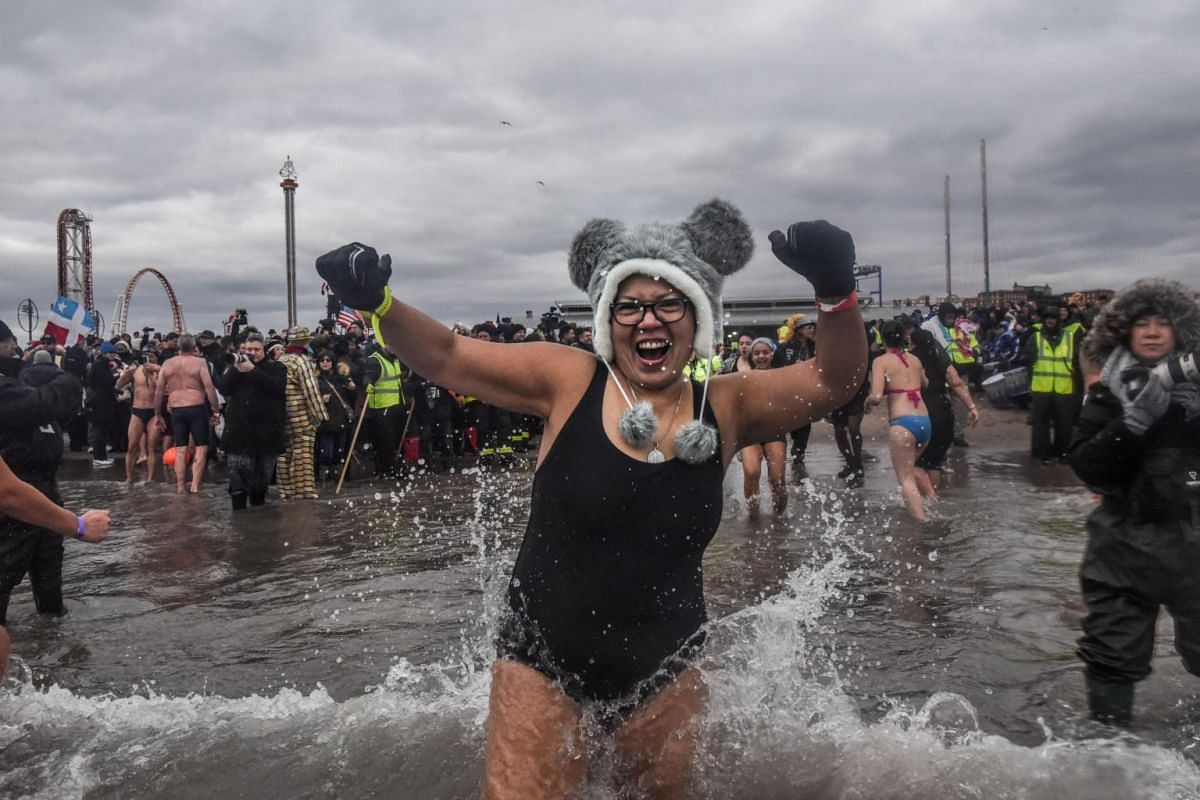 A woman in a swimsuit running into the Atlantic Ocean during the annual Polar Bear plunge on Coney Island.