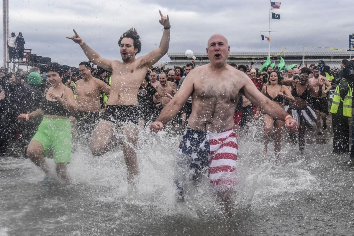 People running into the Atlantic Ocean during the annual Polar Bear plunge on Coney Island.