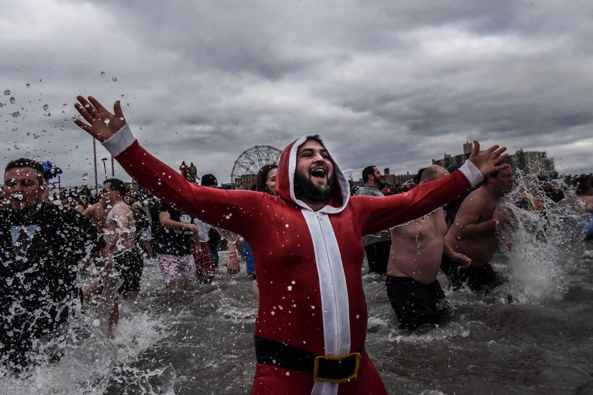 A person dressed in a Santa suit taking part in the Polar Bear plunge on Coney Island.