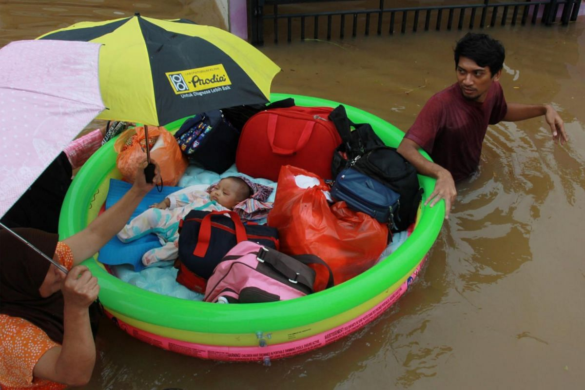 An inflatable pool becomes a boat to evacuate a baby after floods hit a residential area in Tangerang, near Jakarta, Indonesia, on Jan 1, 2020.