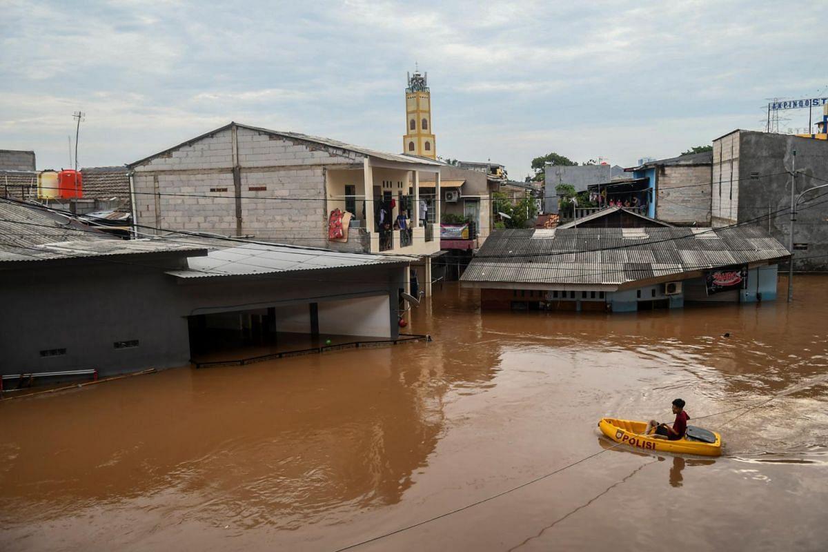 A man pulls himself across floodwaters in a boat in Jakarta, Indonesia, on Jan 1, 2020.
