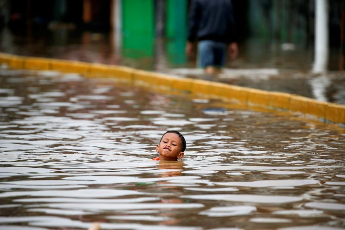 A boy swims in the floodwaters at the Jatinegara area after heavy rains in Jakarta, Indonesia, on Jan 2, 2020.