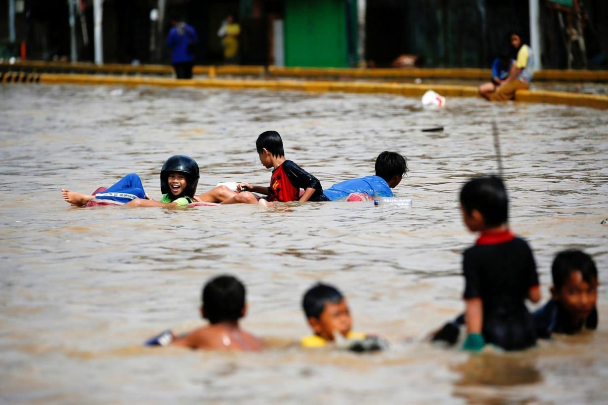 Children play in the floodwaters that hit the Jatinegara area after heavy rains in Jakarta, Indonesia, on Jan 2, 2020.