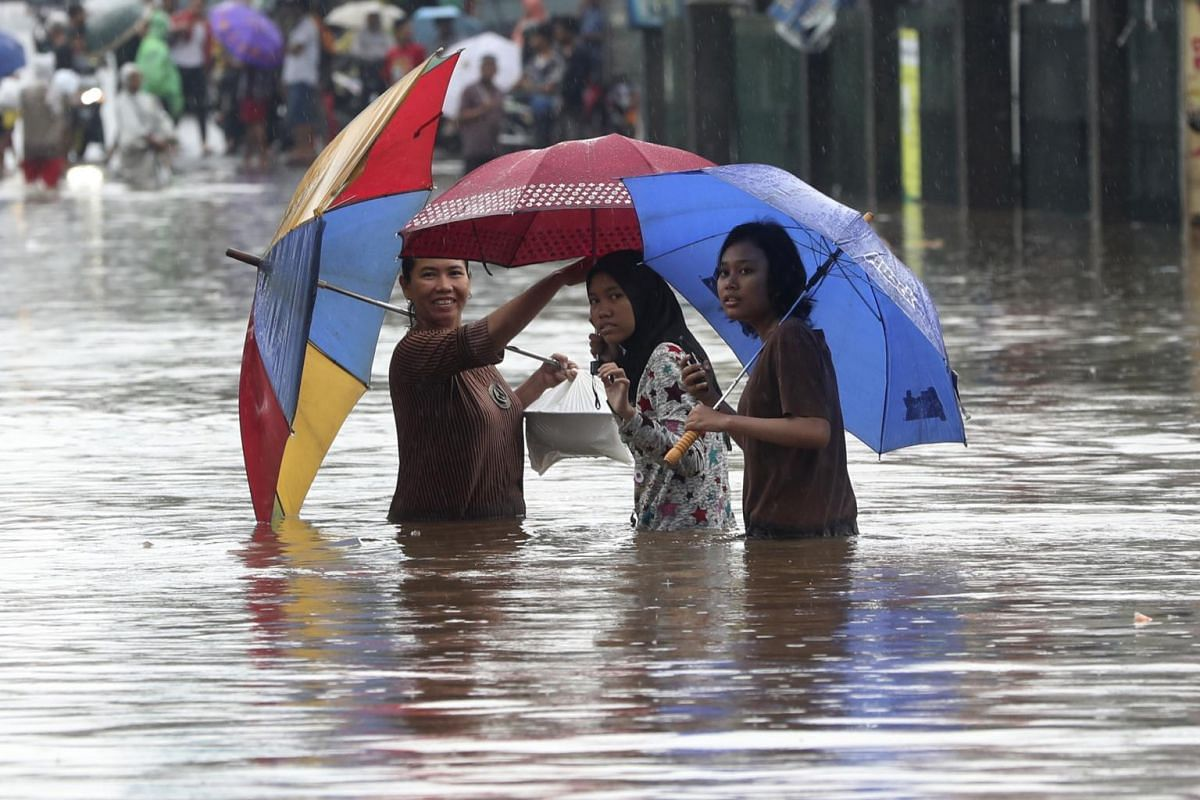 People wade through floodwaters at Jatibening on the outskirts of Jakarta, Indonesia, on Jan 1, 2020.