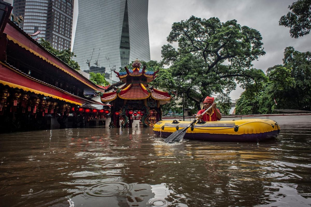 A man uses an inflatable boat after floods hit his monastery in Jakarta, Indonesia, on Jan 1, 2020.