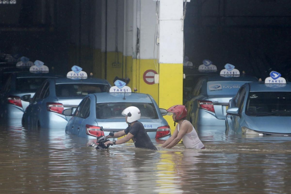 Residents push a motorcycle among submerged taxis on a flooded street in Jakarta, Indonesia, on Jan 1, 2020.