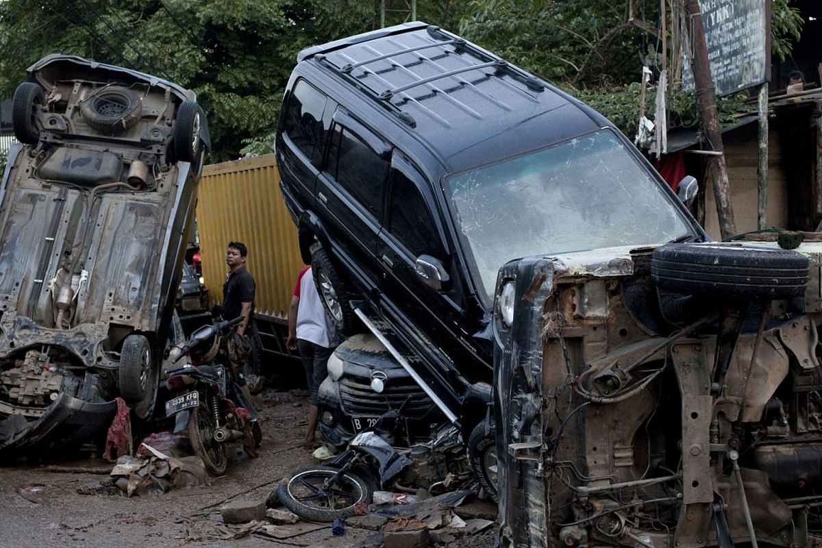 A man inspects wrecked cars that were swept away by flood in Bekasi, West Java, Indonesia, Thursday, Jan. 2, 2020. PHOTO: AP