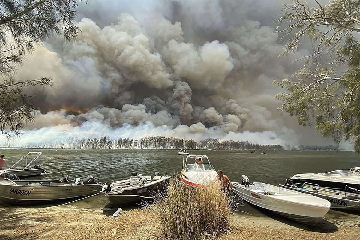 Boats are pulled ashore as smoke and wildfires rage behind Lake Conjola, Australia, Thursday, Jan. 2, 2020. PHOTO: AP