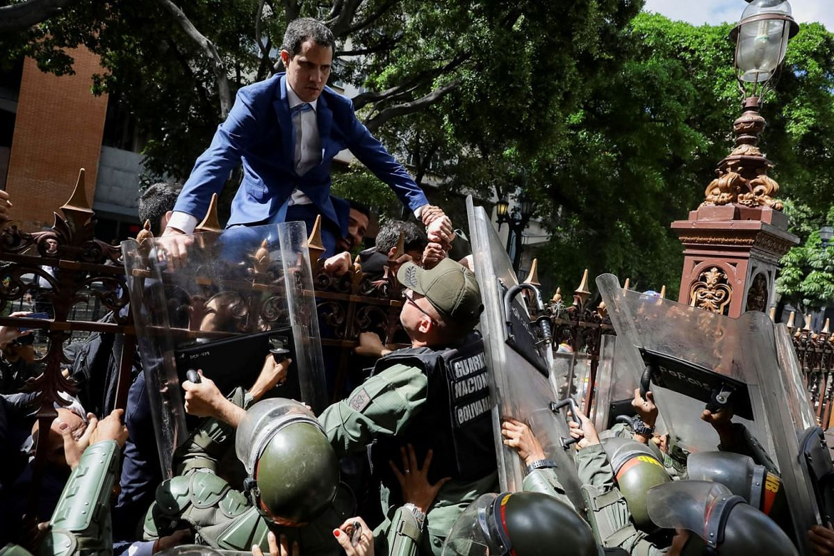 Venezuelan opposition leader Juan Guaido climbs a fence in an attempt to enter the headquarters of the National Assembly, guarded by the police to prevent his entry and that of opposition deputies in Caracas, Venezuela, Jan 5, 2020.