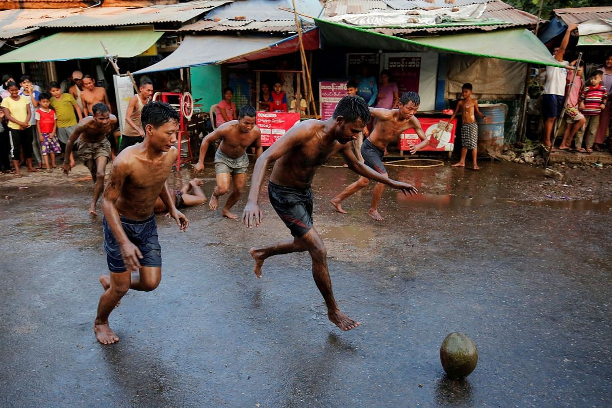 Men play with an oiled coconut in the street during the Independence Day celebrations in Yangon, Myanmar, Jan 4, 2020.