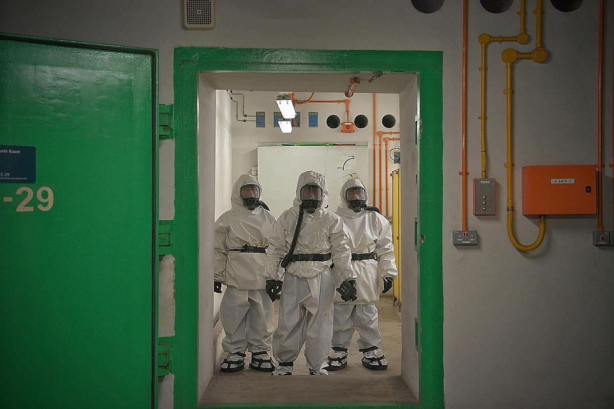 Hazmat – hazardous materials – suits are donned by servicemen manning the decontamination chamber.