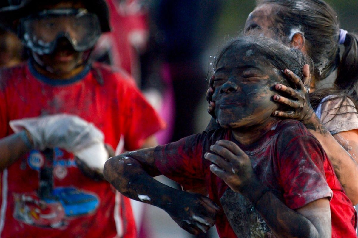 """Children have fun with foam, paint and sprays during the Blacks and Whites Carnival's """"Black Day"""" in Pasto, Colombia, on Jan 5, 2020. The Black and White carnival has its origins in a mix of Andean, Amazonian and Pacific cultural expressions. It is c"""