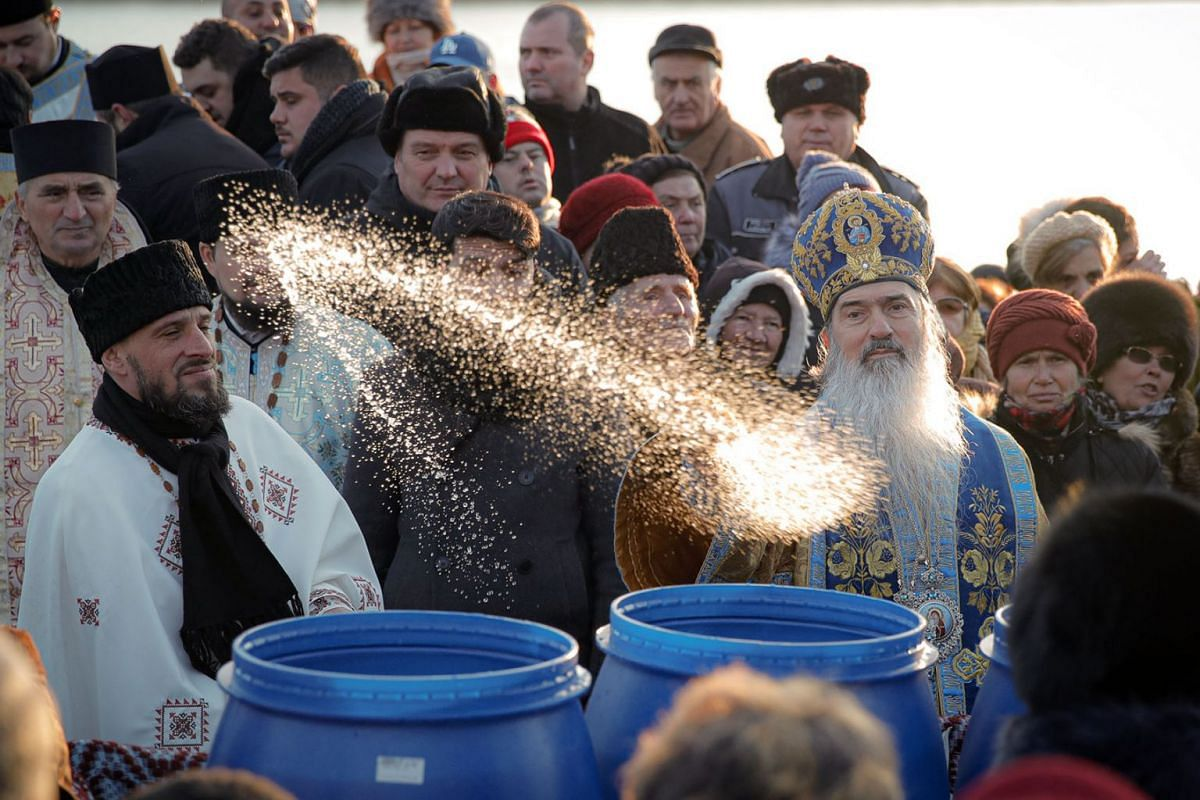 Orthodox archbishop Teodosie blesses people with holy water during a religious service by the Danube river in Harsova, Romania, Jan 5, 2020, a day ahead the celebration of Epiphany. More than 200,000 bottles were filled with holy water in the Black S