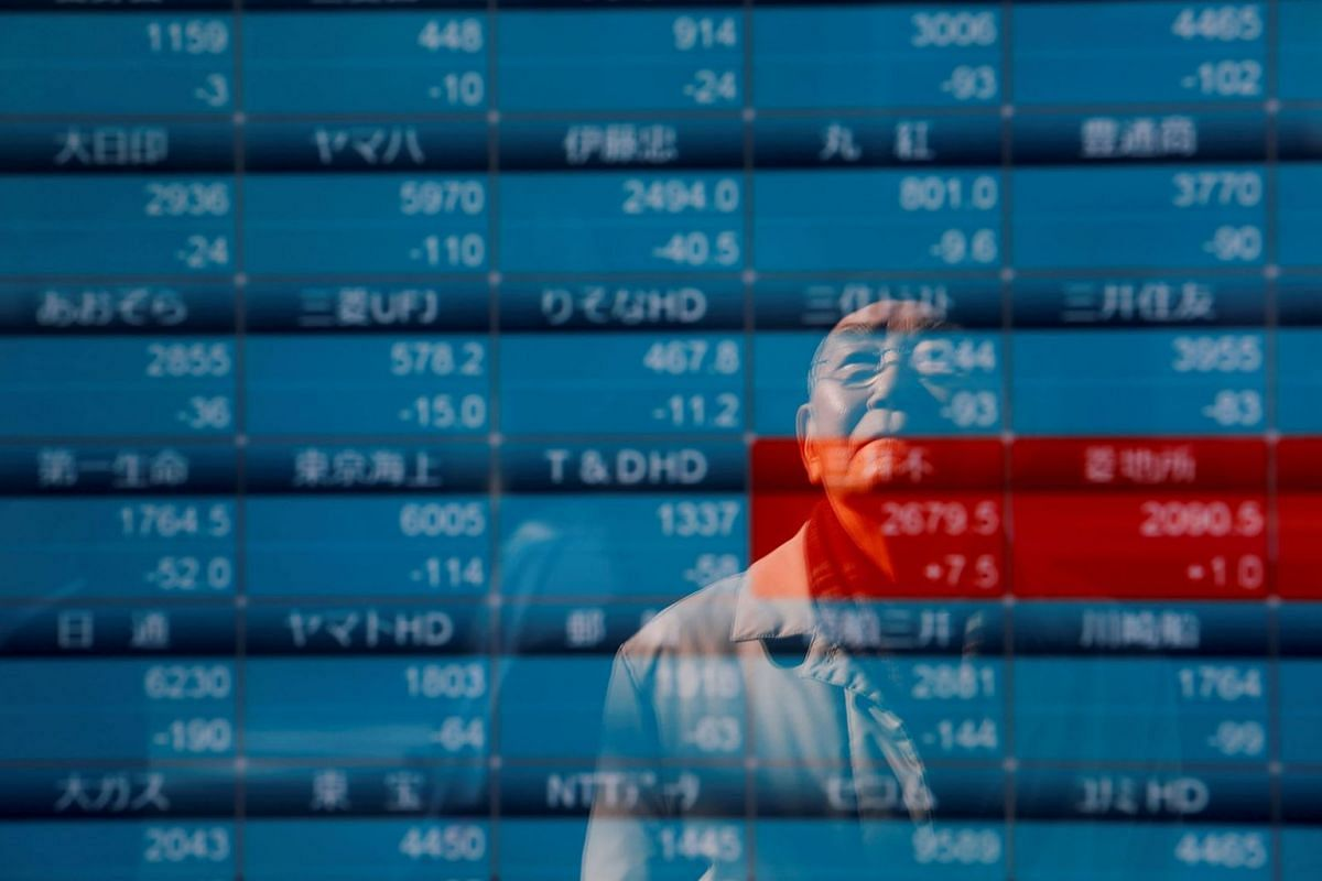 A man is reflected on a board showing stock prices outside a brokerage in Tokyo, Japan, Jan 6, 2020.