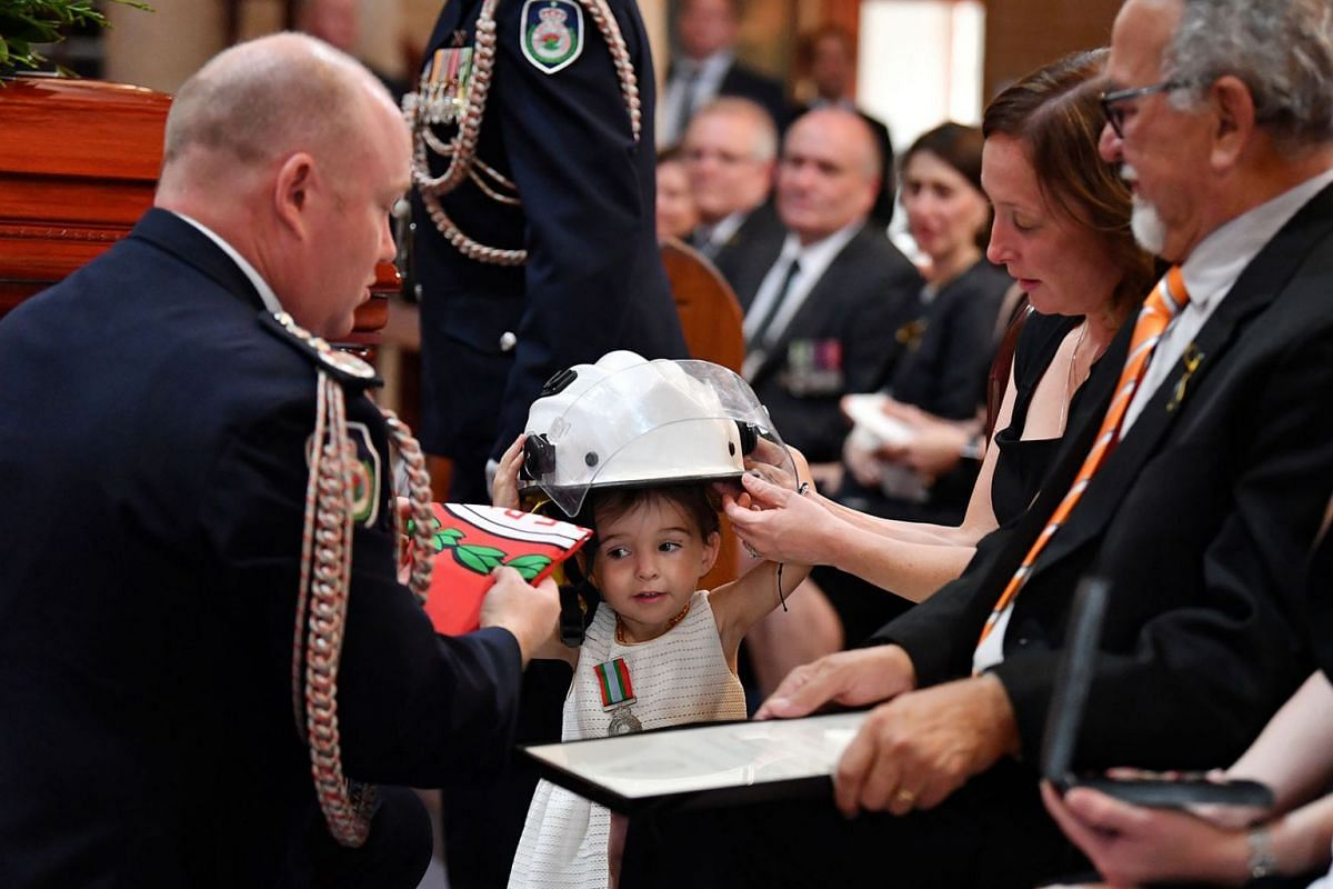 Charlotte O'Dwyer, the daughter of Rural Fire Service volunteer Andrew O'Dwyer, with Andrew's wife Melissa, receives her father's helmet after being presented with her father's service medal by RFS Commissioner Shane Fitzsimmons during the funeral fo
