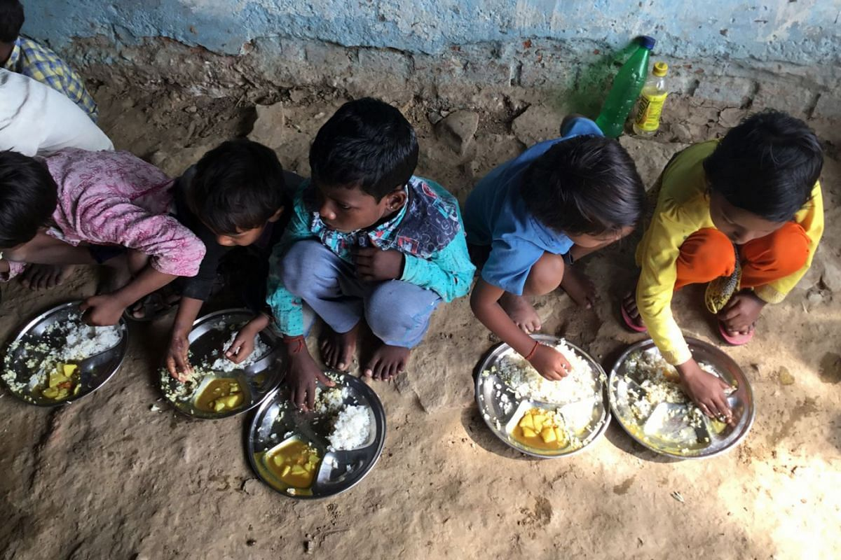 Children eating their frugal lunch of watery potato gravy, accompanied by rice, that the state offers at the local anganwadi and primary school in Madhya Pradesh state in its attempt to curb endemic child malnutrition.