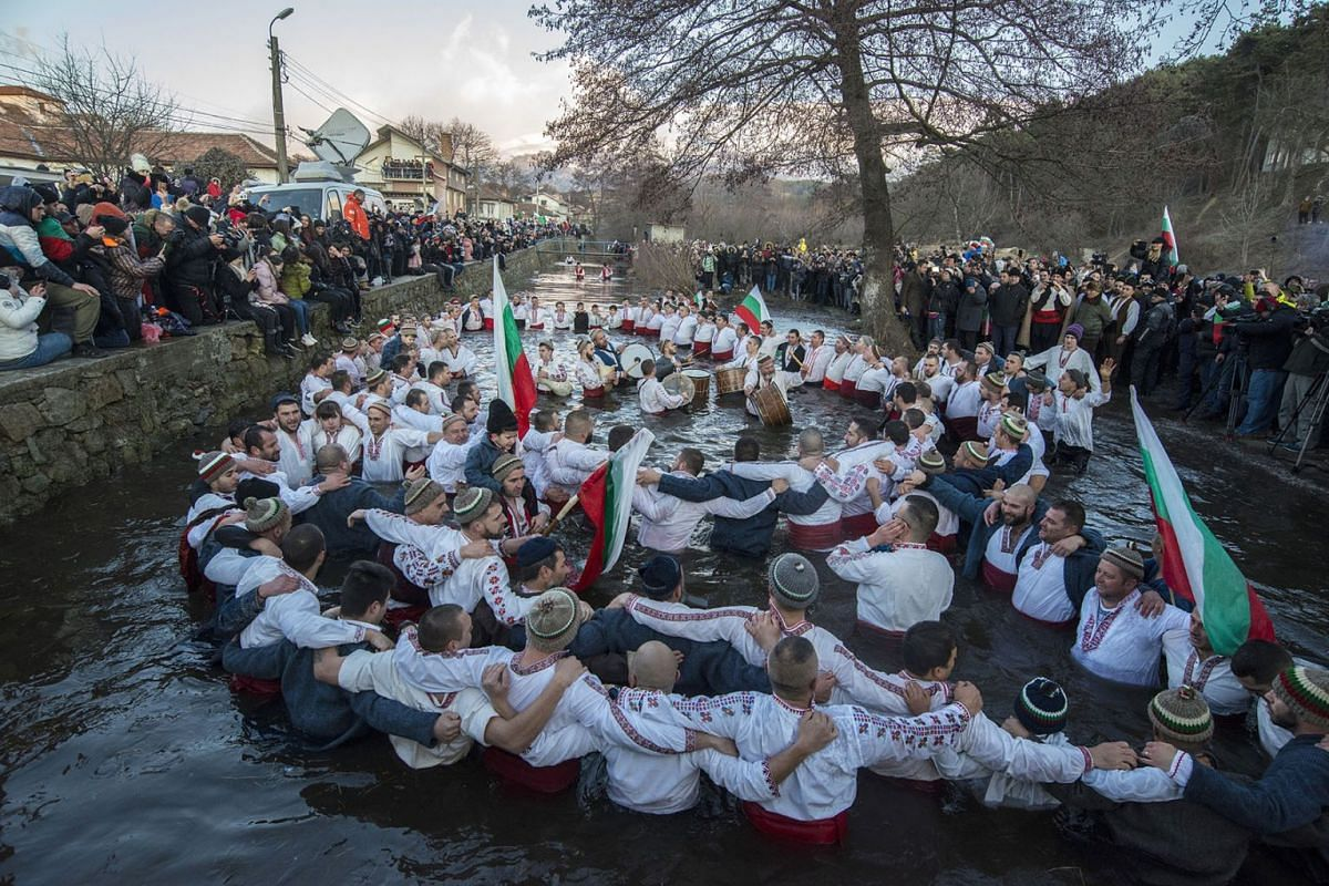 Bulgarians sing and chain dance in the icy waters of the Tundzha river during Epiphany, in Kalofer, Bulgaria, Jan 6, 2020. Thousands of Orthodox Christian worshippers plunged into the icy waters of rivers and lakes across Bulgaria on Monday to retrie
