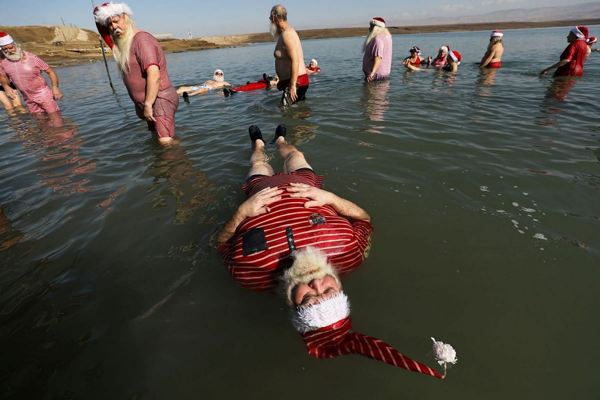 A man, part of a group of trained Santa Clauses from various countries, wears a Santa Claus-themed bathing suit as he floats in the Dead Sea, at Neve Midbar beach in the Israeli-occupied West Bank, Jan 7, 2020.